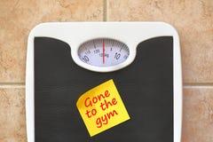 体重计与去健身房备忘录贴纸 图库摄影