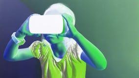 体验VR在五颜六色的背景的少女耳机比赛 虚拟的技术 免版税图库摄影