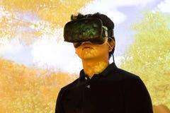 体验VR虚拟现实娱乐尖头棒的亚裔少年 库存图片