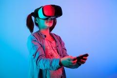 体验VR虚拟现实耳机的女孩 免版税库存照片