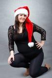 体贴握她的肚子的美丽的怀孕的圣诞老人妇女 免版税库存图片