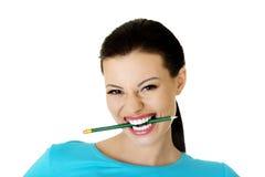 体贴的可爱的学生妇女尖酸的铅笔 免版税库存图片