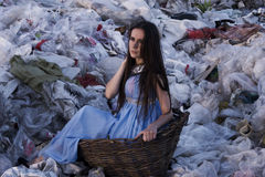 体贴的女孩在一个老篮子特写镜头的垃圾填埋坐 免版税库存图片
