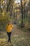 体贴的女孩在秋天森林里 免版税库存图片