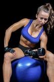 体贴的妇女举的哑铃,当坐锻炼球时 图库摄影