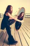 体贴的妇女看在镜子的反射 库存照片