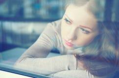 体贴的悲伤女孩是哀伤的在窗口 免版税库存图片