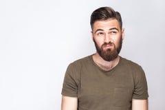 体贴的有胡子的人画象有深绿T恤杉的反对浅灰色的背景 免版税图库摄影