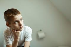 体贴的男小学生坐洗手间和查寻 库存图片