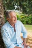 体贴的退休的人坐树干 免版税库存照片