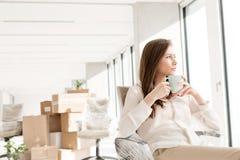 体贴的年轻女实业家食用在椅子的咖啡在新的办公室 免版税图库摄影