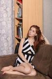 体贴的年轻美丽的红头发人妇女坦率的画象坐接触她华美的头发典型的室背景的沙发 免版税库存照片
