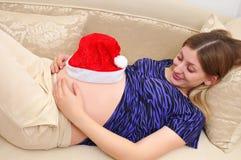 体贴看起来怀孕的妇女的腹部 图库摄影