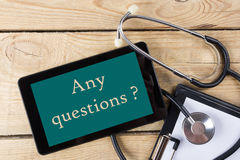 任何问题?-医生的工作场所 片剂,听诊器,在木书桌背景的剪贴板 顶视图 库存图片