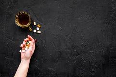 余醉未醒而难受的综合症状 alcoholisms 玻璃和药片在黑背景顶视图拷贝空间 免版税库存照片