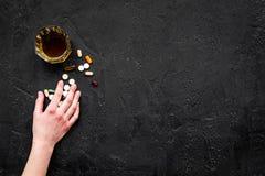 余醉未醒而难受的综合症状 alcoholisms 玻璃和药片在黑背景顶视图拷贝空间 库存图片
