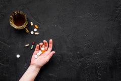 余醉未醒而难受的综合症状 alcoholisms 玻璃和药片在黑背景顶视图拷贝空间 免版税图库摄影