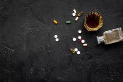 余醉未醒而难受的综合症状 alcoholisms 玻璃和药片在黑背景顶视图拷贝空间 免版税库存图片