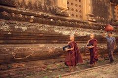 佛教新手修士走的施舍在Bagan 免版税库存照片