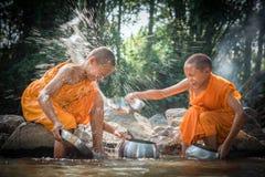 佛教新手清洗碗并且飞溅在s的水 免版税库存照片