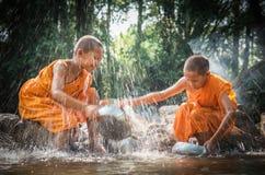 佛教新手清洗碗并且飞溅在s的水 免版税图库摄影