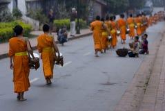 佛教新手走收集施舍和课程,琅勃拉邦,老挝。 免版税图库摄影