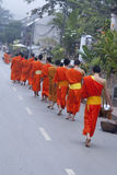 佛教新手走收集施舍和课程,琅勃拉邦,老挝。 免版税库存图片