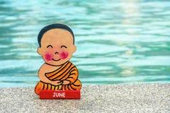 佛教男孩在度假坐在莲花坐愉快的夏天的在水池的边缘 o 签字与 库存照片