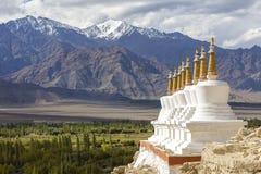 佛教chortens、白色stupa和喜马拉雅山山在背景中在Shey宫殿附近在拉达克,印度 库存图片