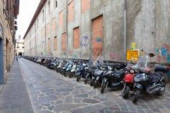佛罗伦萨,意大利2016年9月11日:当地居民很多滑行车和脚踏车在狭窄的街道停放在佛罗伦萨 免版税图库摄影
