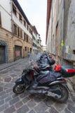 佛罗伦萨,意大利2016年9月11日:当地居民很多滑行车和脚踏车在狭窄的街道停放在佛罗伦萨 免版税库存图片