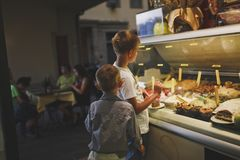 佛罗伦萨,意大利7月20日2014年 男孩选择各种各样的冰淇凌或点心在咖啡馆在一个玻璃窗里 免版税库存图片