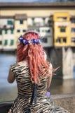 佛罗伦萨,意大利- 2013年7月14日;有拍Ponte Vecchio,在亚诺河的著名老桥梁的照片色的头发的一名妇女 库存图片