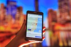 佛罗里达地图电话的在夜城市的背景中 关闭拿着手机的妇女手 库存照片