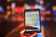 佛罗里达地图电话的在夜城市的背景中 关闭拿着手机的妇女手 库存图片