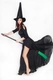 作为一个巫婆打扮的少妇在被隔绝的背景的万圣夜 免版税图库摄影