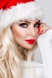作为一个红色盖帽的圣诞老人穿戴的美好的性感的白肤金发的女性模型 库存图片