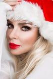 作为一个红色盖帽的圣诞老人穿戴的美好的性感的白肤金发的女性模型 图库摄影