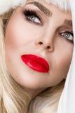 作为一个红色盖帽的圣诞老人穿戴的美好的性感的白肤金发的女性模型 免版税库存照片
