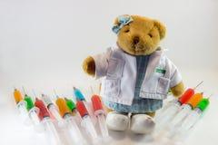 作为一位妇女医生的玩具熊有包含多色解答和白色背景的塑料医疗注射器的 `医疗概念` 库存图片