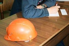 作为一位工程师的人工作有在桌上的一件橙黄色盔甲的学习,写在笔记本在一套工厂设备 图库摄影