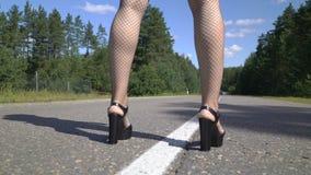 作为一名性感的警察打扮的美丽的少妇 女警在中间路线站立,停止一辆红色汽车 女性 股票录像