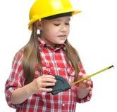作为一名建筑工人的女孩有卷尺的 免版税图库摄影