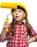 作为一名建筑工人的女孩有漆滚筒的 免版税图库摄影
