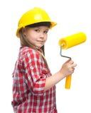 作为一名建筑工人的女孩有漆滚筒的 图库摄影