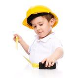 作为一名建筑工人的男孩有卷尺的 库存图片