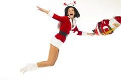 作为一白色backgrou的圣诞老人打扮的美丽的少妇 免版税库存图片