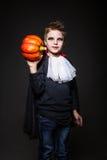 作为万圣夜党和拿着的橙色南瓜一个吸血鬼打扮的逗人喜爱的孩子 库存照片