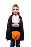 作为万圣夜和拿着的南瓜篮子一个吸血鬼打扮的逗人喜爱的男孩 免版税图库摄影