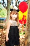 作为与气球的一只猫打扮的美丽的小女孩在手上 甜微笑,嫩神色 免版税库存图片